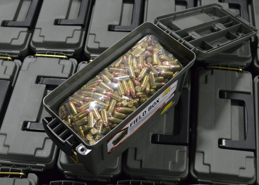 Plano ammo can filled with 9mm rounds sitting on a pallet of other cans.